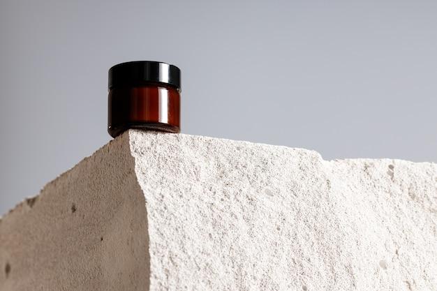 Skincare cosmetic jar on gray cinder block close up
