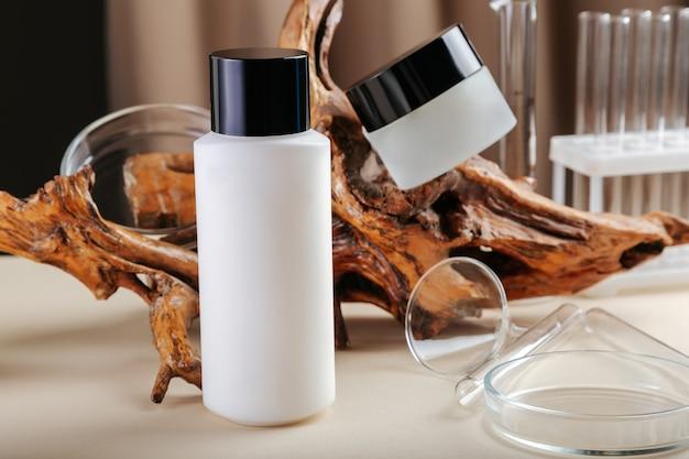 スキンケア化粧品キット。木と実験用ガラス器具を使ったベージュ色の表面のスキンケア用クリームとクレンザーのキット。スキンケア化粧品セットの商品撮影。天然エコウッド