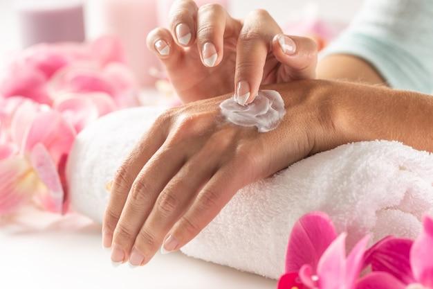 Косметика по уходу за кожей в виде лосьона для рук, наносимого на руки женщины.