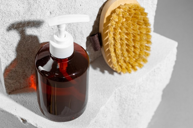 Skincare cosmetics and massage brush on grey background close up