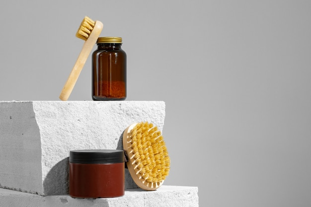 Skincare cosmetics and massage brush on grey close up