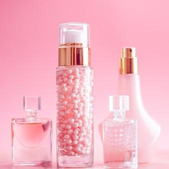 ピンクの背景に設定されたスキンケア香水とメイクアップ高級美容と化粧品