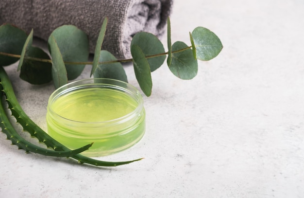 Skincare product gel aloe vera in jar and eucalyptus leaves on table