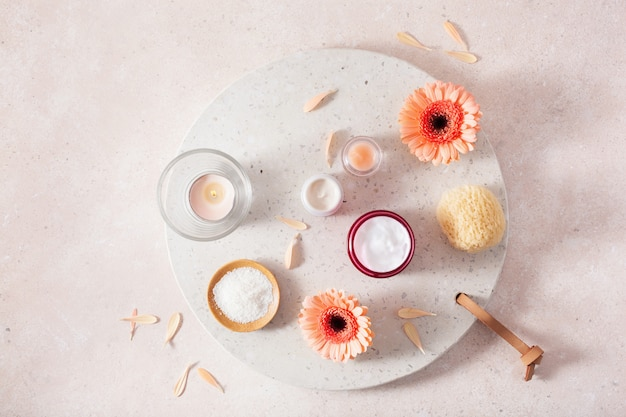 スキンケア製品とデイジーの花。家庭用スパトリートメントのための自然化粧品