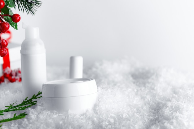 Skincare products bottles on snow covered surface.