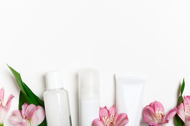Skincare products bottles with lily flowers bottom border.