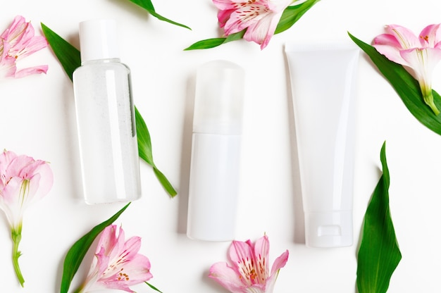 Skincare products bottles with lily flowers. cream tube, concealer dispenser, micellar water