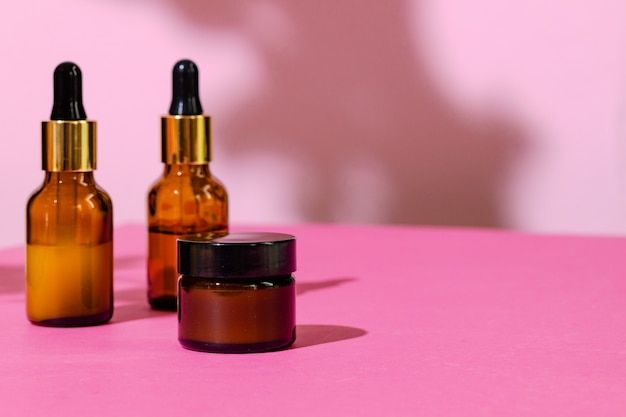 Skincare products containers on bright pink background