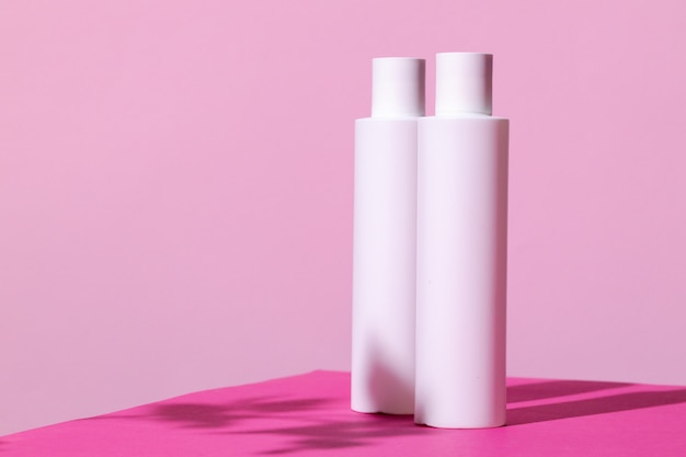 Skincare products containers on bright pink