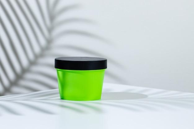 創造的な影と白い背景の上のスキンケア製品コンテナをクローズアップ
