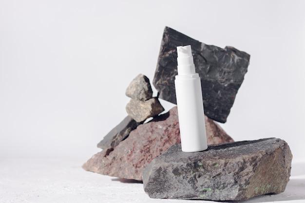 Уход за кожей белая пластиковая бутылка с дозатором и флаконы на фоне камней изолированы