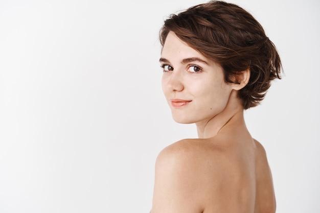 Cura della pelle. la vista posteriore della giovane donna caucasica gira la testa all'indietro, in piedi mezza nuda sul muro bianco e sorridente. ragazza tenera senza trucco e bellezza naturale