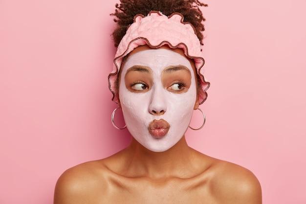 스킨 케어 루틴. 아름다운 아프리카 계 미국인 여성은 입술을 둥글게 유지하고, 영양 마스크를 얼굴에 바르고, 여드름 발생 가능성을 줄이며, 뷰티 트리트먼트로 삶의 즐거움을 거의 얻지 못하고 피부를 개선합니다.