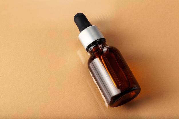 Бутылка сыворотки по уходу за кожей на светло-бежевом фоне крупным планом