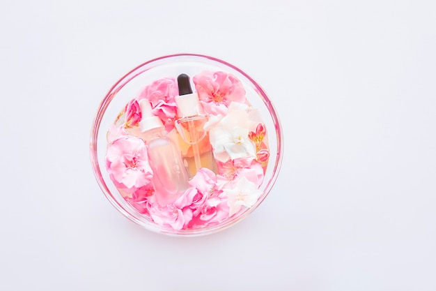 Skincare serum oil with little flowers in glass plate. natural cosmetology, skin treatment.