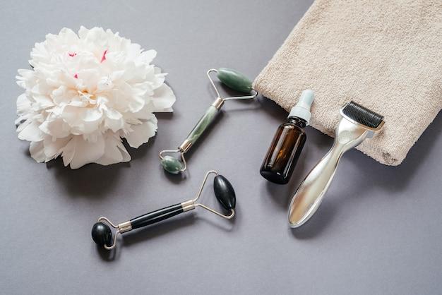 스킨케어 도구: 마이크로니들링 더마 롤러, 옥 구아샤 마사지 롤러, 흰색 모란 꽃이 있는 회색 배경에 혈청 병
