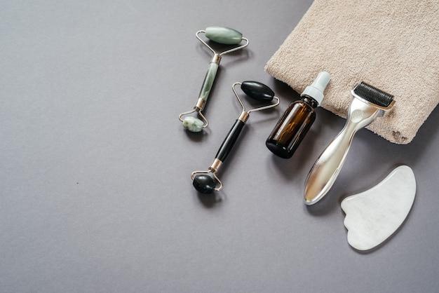 스킨케어 도구: 마이크로니들링 더마 롤러, 옥 구아샤 마사지 롤러 및 회색 배경에 혈청 병