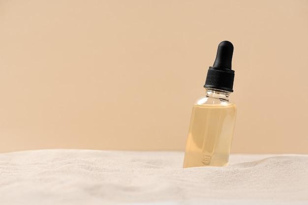 美容美容フェイスセラムによるスキンケア。砂と自然な背景にピペットとガラス瓶。ドライスキンケア製品。体の肌に潤いを与えるエッセンシャルオイル。スペースをコピーします。