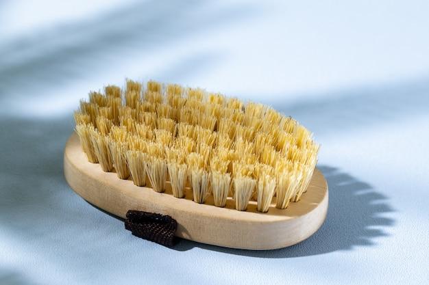 Skincare wooden massage brush on gray close up