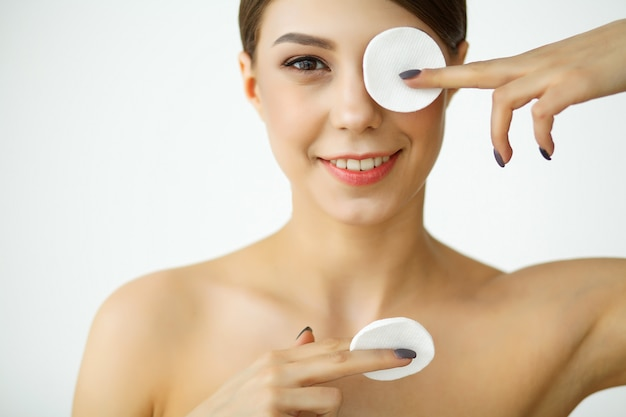 Skincare. young woman with lotion washing face at bathroom