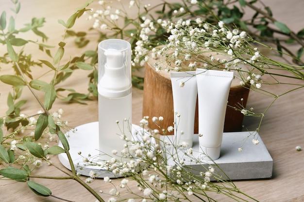 Контейнеры косметической бутылки упаковывая с зелеными травяными листьями, пустой ярлык для органического клеймить, естественная концепция продукта красоты skincare.
