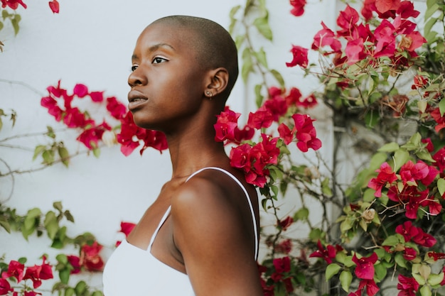 Skinhead woman surrounded by red flowers