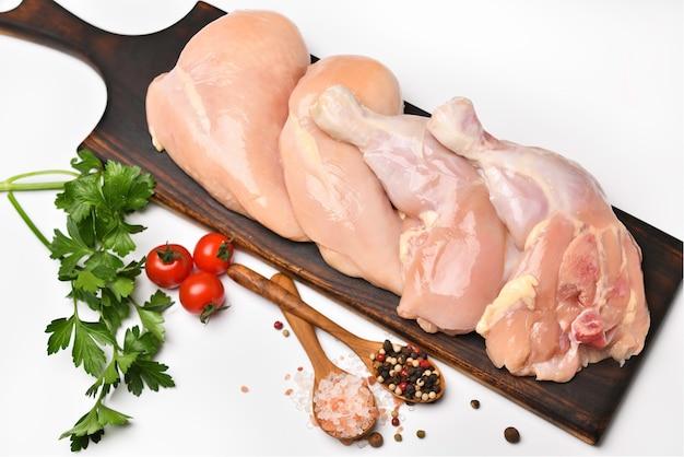 흰색 표면에 나무 커팅 보드에 요리 재료로 껍질을 벗긴 생 닭 허벅지