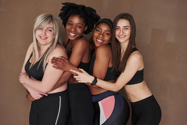 細くて大きい。茶色の空間に立っている多民族の女性のグループ