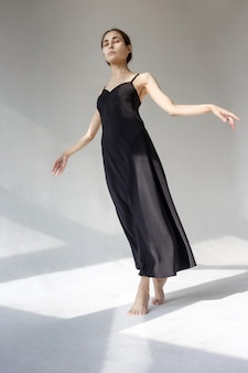 Skinny asian ballet dancer in black dress stands on white emty cyclorama in pattern of light and shadow. peace and joy