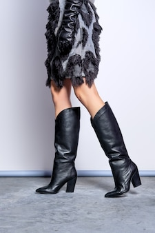 Skinny female legs in oversize high boots