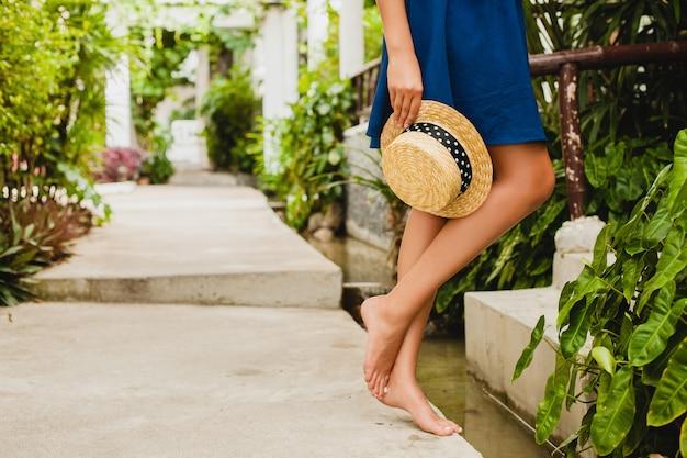 麦わら帽子を保持している青いドレスのセクシーなスリムな若い女性の細い足