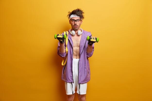 L'uomo magro ha l'obiettivo di un corpo muscoloso perfetto, solleva i manubri e guarda con espressione scioccata, indossa cuffie e abbigliamento sportivo, si allena in palestra, sorpreso di perdere peso, ha un duro allenamento