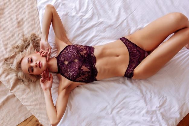 スキニーモデル。ベッドの上でポーズをとる濃い赤のレースのブラを身に着けているスキニー魅力的な有望な写真モデル