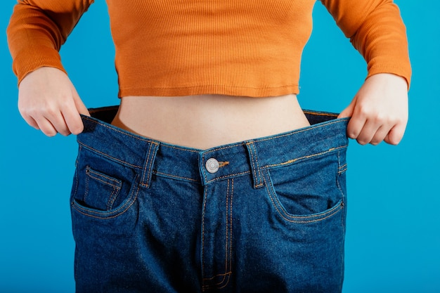 Skinny weight loss woman show flat stomach pulling by hands oversized big blue pants jeans. slim body low fat healthy size athletic girl isolated over blue color background.