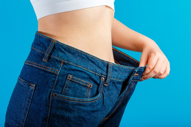 Skinny weight loss woman show flat stomach pulling oversized big blue pants jeans. slim body low fat healthy size athletic girl isolated over blue color background. copy space.
