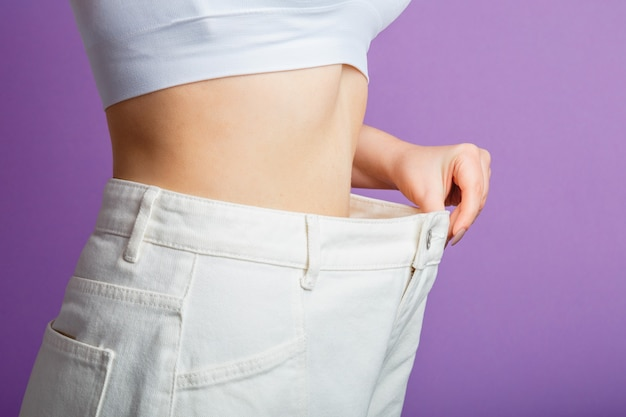 Skinny weight loss woman show flat stomach pulling oversized big white pants jeans. slim body low fat healthy size athletic girl isolated over purple color background. copy space.