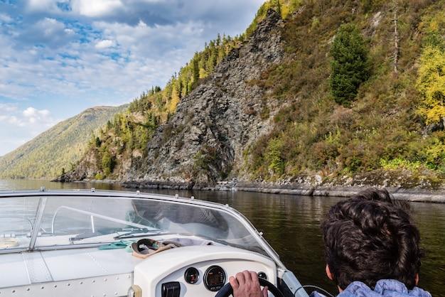 コックピットからのモーターボートビューの舵取りのスキッパー秋ロシアアルタイ共和国テレツコイ湖