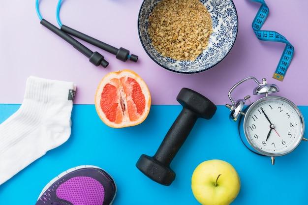 Skipping rope; measuring tape; sock; dumbbell; shoes; apple; halved orange fruit; alarm clock on dual backdrop
