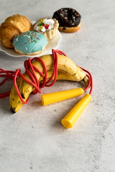 Skipping rope rolled with banana and delicious dessert on plate over concrete background