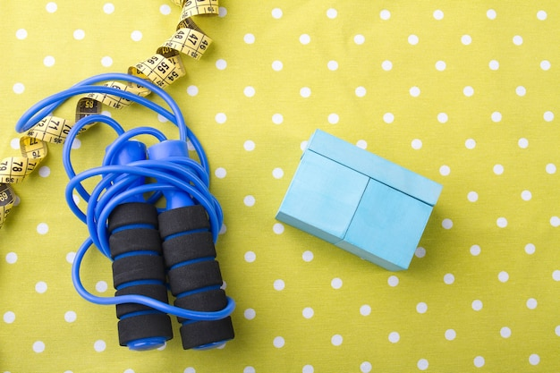 Skipping rope with measuring tape and cupboard on dotted yellow background flat lay composition
