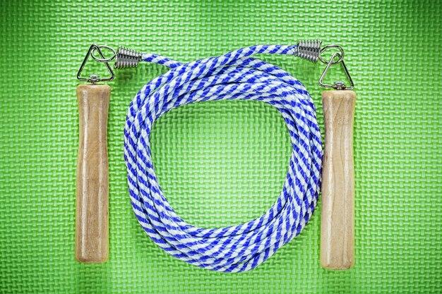 緑の背景のフィットネスの概念に木製ハンドル付き縄跳び