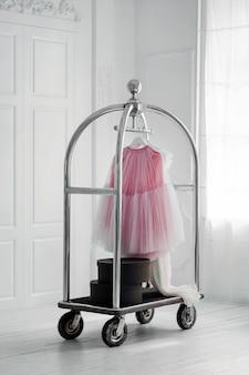 Юбка висит на передвижной вешалке в минималистском интерьере белой комнаты.