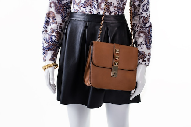 Skirt and purse on mannequin. woman's brown leather handbag. dark skirt with trendy purse. party outfit for stylish girls.