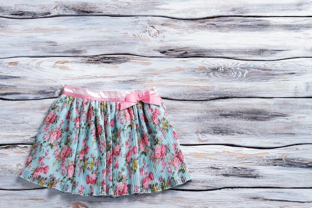 핑크 플라워 프린트 스커트. 활과 화려한 여름 치마입니다. 흰색 테이블에 짧은 치마. 여아의 새 옷이 입고되었습니다.