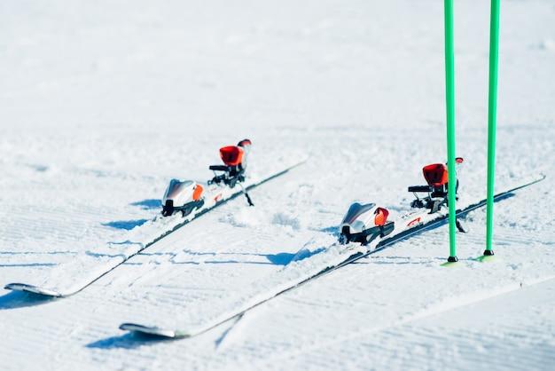 雪のクローズアップから突き出ているスキーとポール、誰も。冬のアクティブスポーツコンセプト。マウンテンスキー用具