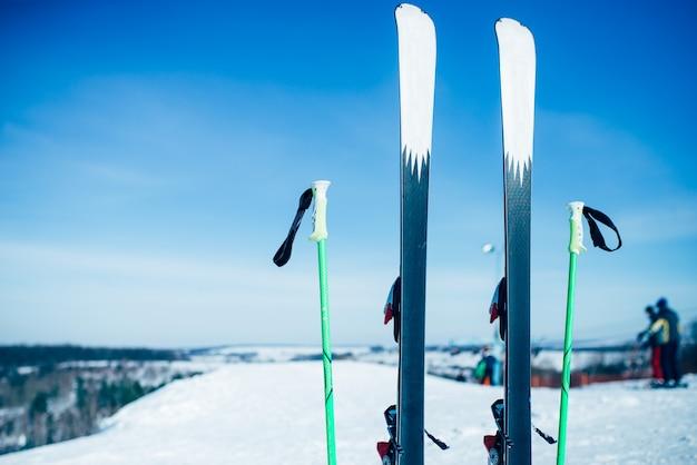 雪から突き出たスキー板とポール、だれも。冬の極端なスポーツコンセプト。マウンテンスキー用具