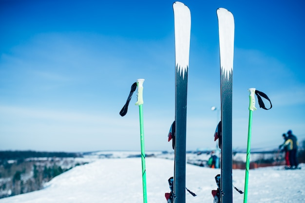 Skis and poles sticking out of the snow, nobody. winter extreme sport concept. mountain skiing equipment