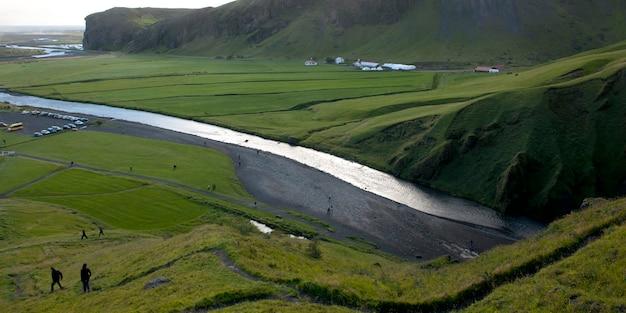 Skoga river through cliffs and farmland with hikers