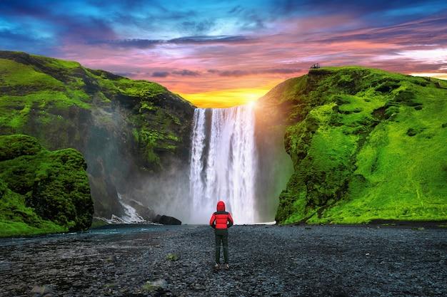 Водопад скогафосс в исландии. парень в красной куртке смотрит на водопад скогафосс.