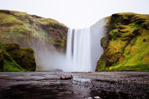 Красивый водопад между зелеными холмами в skogafoss, исландия